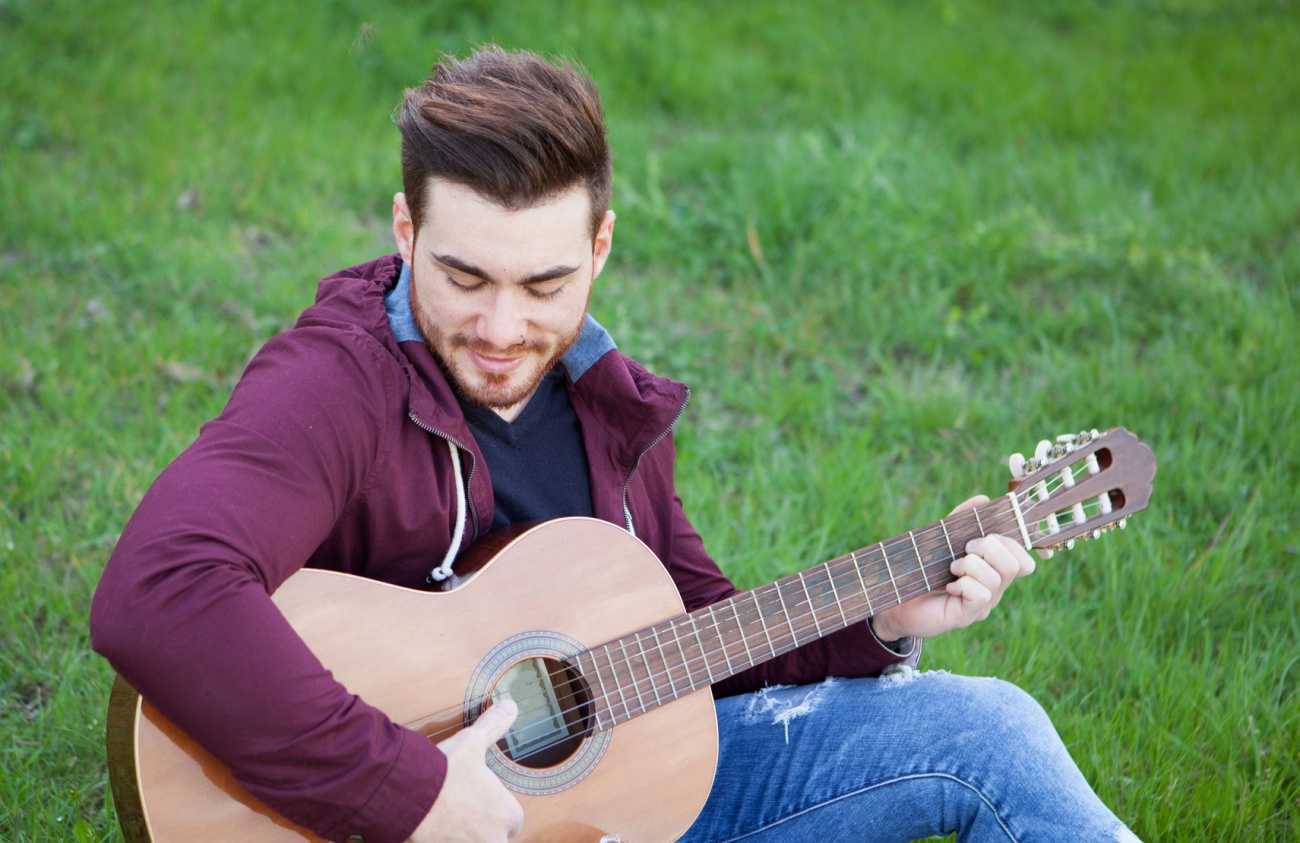 Cool handsome guy playing guitar at outside