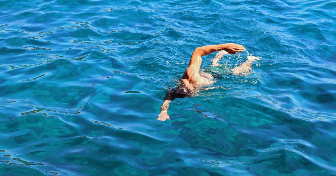 Strong athletic man swimming butterfly style in the sea. Active summer holiday vacation. Sport, healthy lifestyle concept