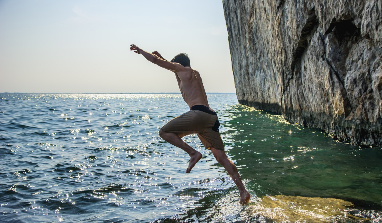 Young shirtless athletic man jumping in water by ocean shore